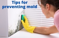 woman cleaning mold from a wall with a sponge